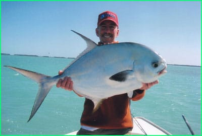 charter guest holding a big permit fish